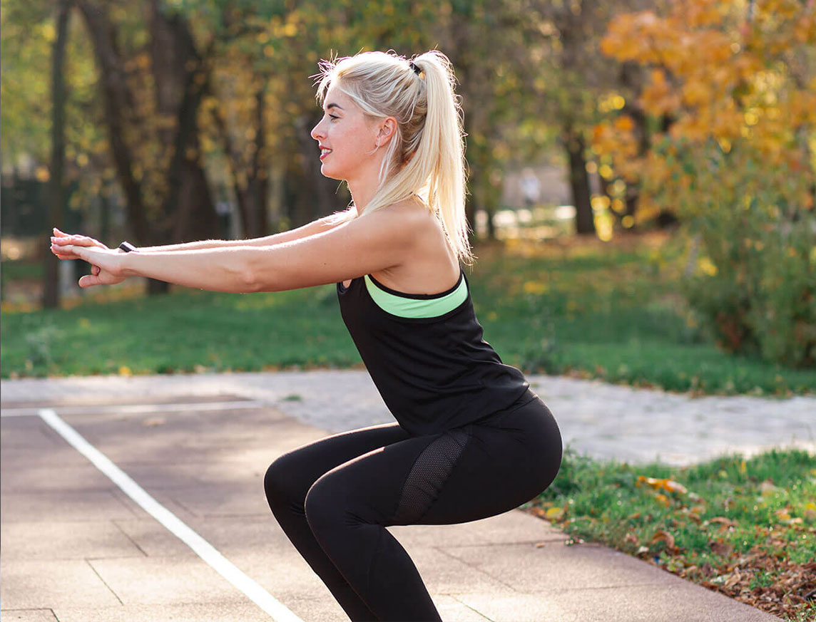 blonde woman doing squats in the park