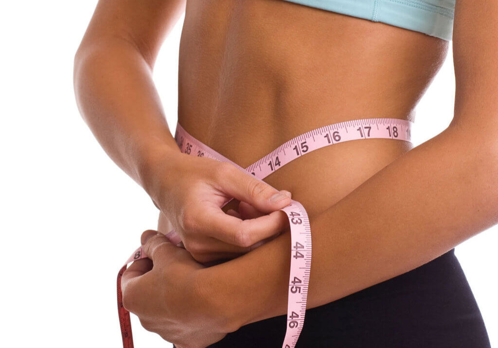 woman measuring her belly with a tape measure